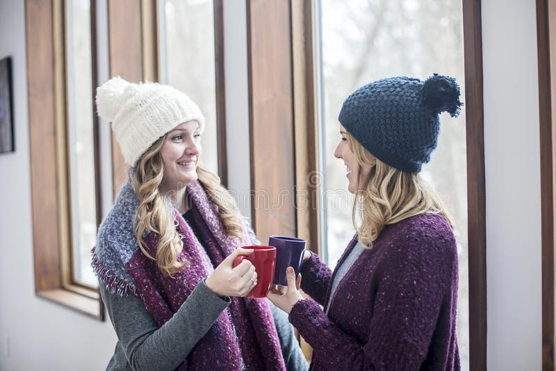 Happy women friends at home in winter. Two smiling young women standing by window at at home in winter holding mugs of coffee or tea stock photo