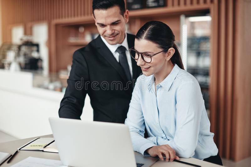 Smiling businesspeople working together on a laptop in an office stock photo