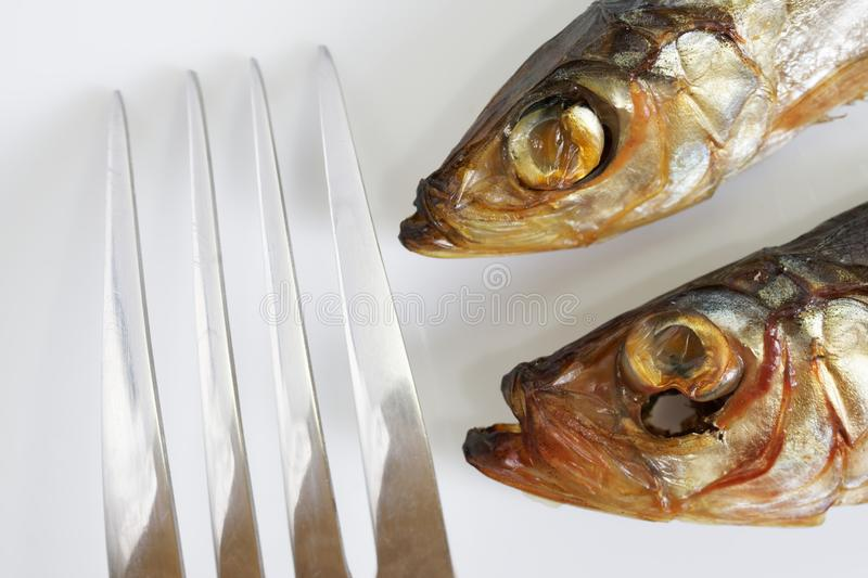 Two smoked Baltic herring and a metal fork on a white background. Close-up. Macro stock photos