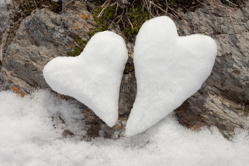 Two snow hearts on rock