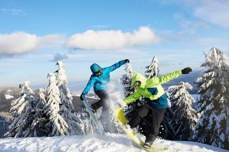 Two snowboarders doing tricks at ski resort. Riders friends performing jump with their snowboards near forest on stock photography