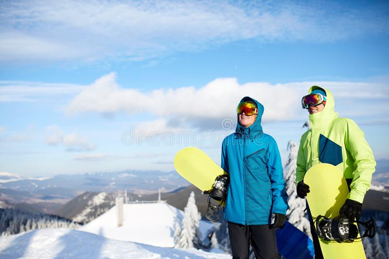 Two snowboarders posing at ski resort. Riders friends carrying their snowboards through forest for backcountry freeride stock photo