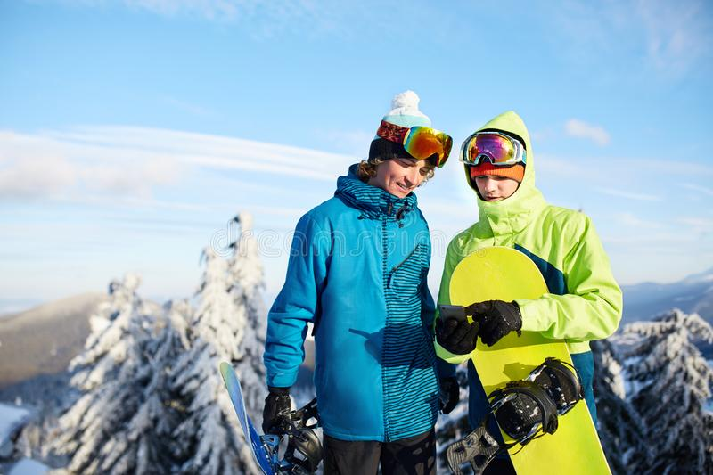 Two snowboarders talking and holding smartphones. Friends looking at cellphone and communicating in social network. Sharing their photos in app with internet stock image
