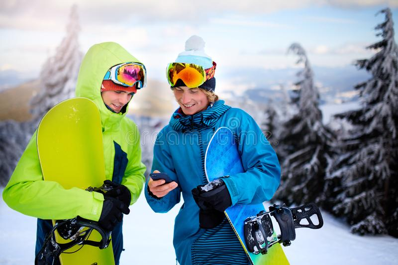 Two snowboarders talking and holding smartphones. Friends looking at cellphone and communicating in social network royalty free stock photos
