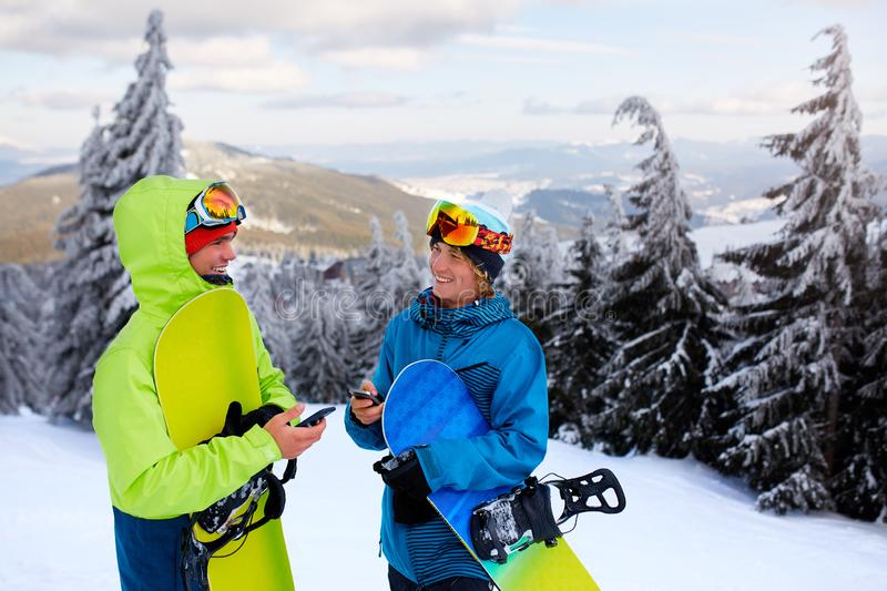 Two snowboarders talking and holding smartphones. Friends looking at cellphone and communicating in social network. Sharing their photos in app with internet royalty free stock image