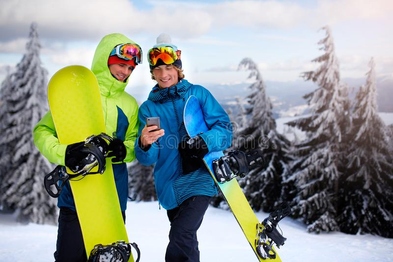 Two snowboarders talking and holding smartphones. Friends looking at cellphone and communicating in social network. Sharing their photos in app with internet stock photography