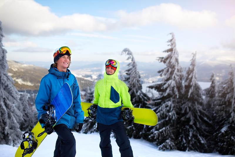 Two snowboarders walking at ski resort. Friends climbing to mountain top carrying their snowboards through forest for royalty free stock photos