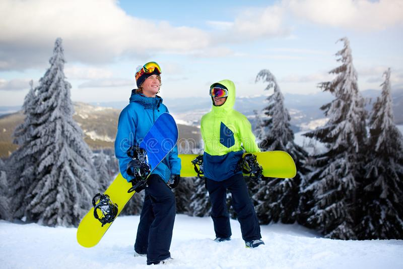 Two snowboarders walking at ski resort. Friends climbing to mountain top carrying their snowboards through forest for royalty free stock images