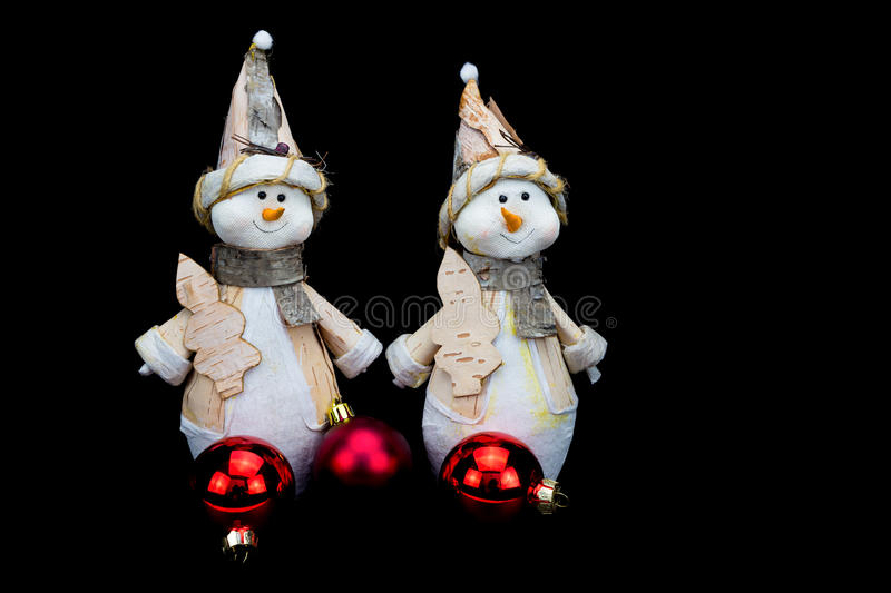 Two snowmen figurines with red baubles on black royalty free stock images