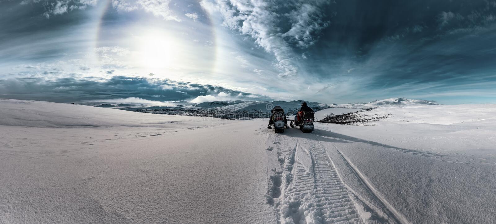 Two snowmobiles with one driver stand in front of dramatic scenic view at cold snowy Norwegian Mountains, Sun halo shines on cold royalty free stock images