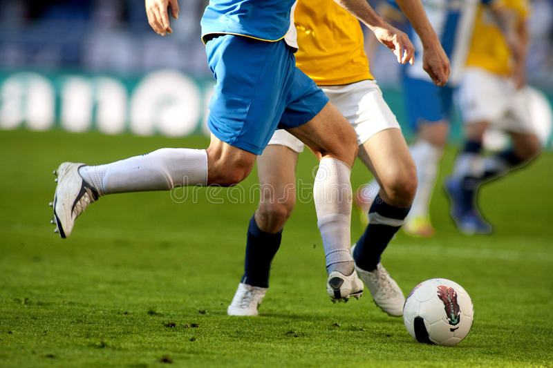 Two soccer players vie. Legs of two soccer players vie on a match stock photography