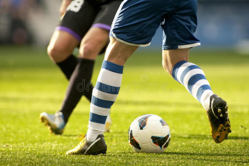 Two soccer players vie. Legs of two soccer players vie on a match royalty free stock image