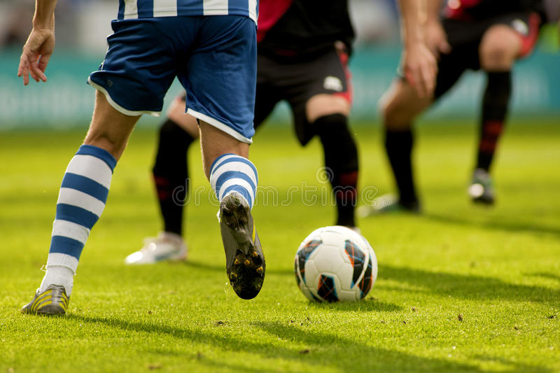 Two soccer players vie. Legs of two soccer players vie on a match stock image