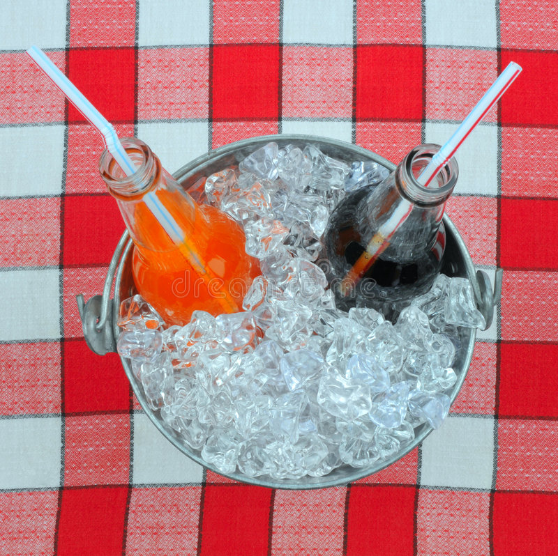 Two Soda Bottles in Bucket of Ice. On Picnic Table Cloth stock photography
