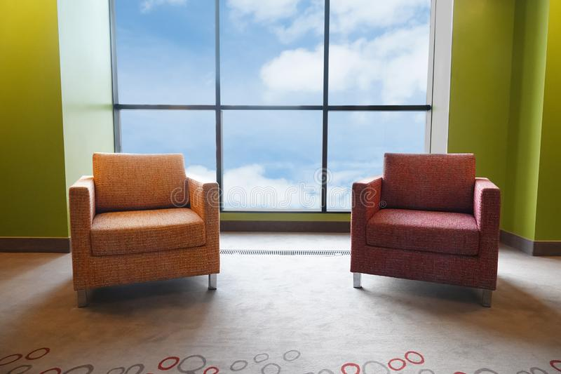 Two soft chairs in  large panoramic window. View of the sky and clouds. Two soft chairs in a large panoramic window. View of the sky and clouds royalty free stock photo