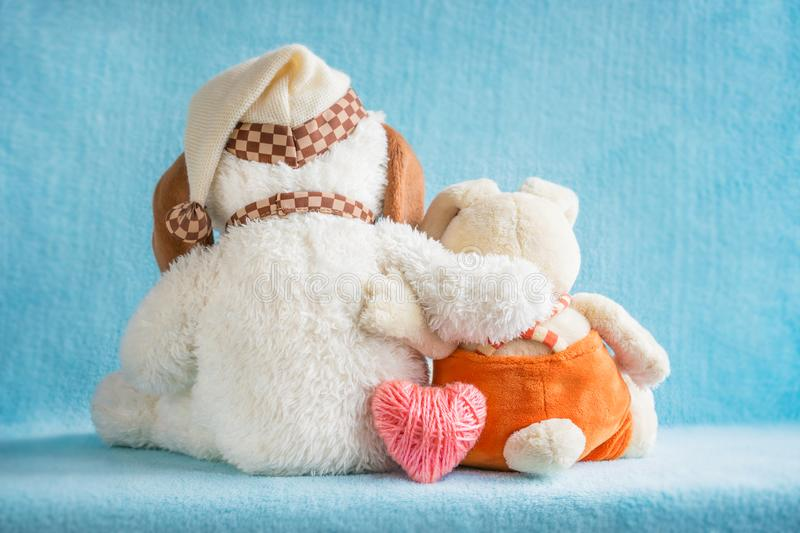 Two soft toy dog and rabbit embrace and a pink knitted heart on. A blue background. Two cute embracing toys puppy and bunny sitting together - girl and boy stock images