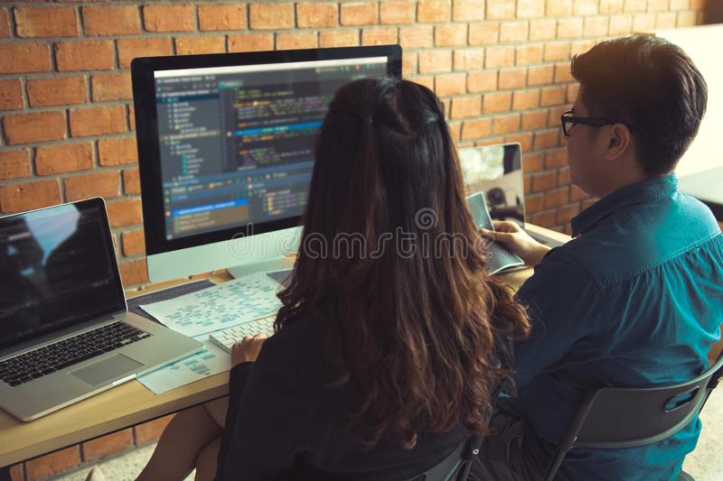 Two software developers are using computers to work together with their partner at the office desk.  royalty free stock photography