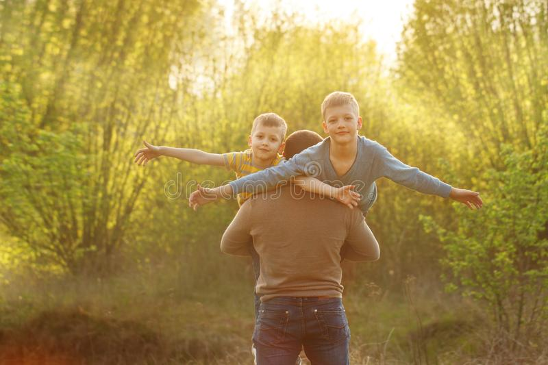 Two sons and his spring in winter forest, outdoor portrait. Father holding two sons. fun, joy, happiness, friendship stock image