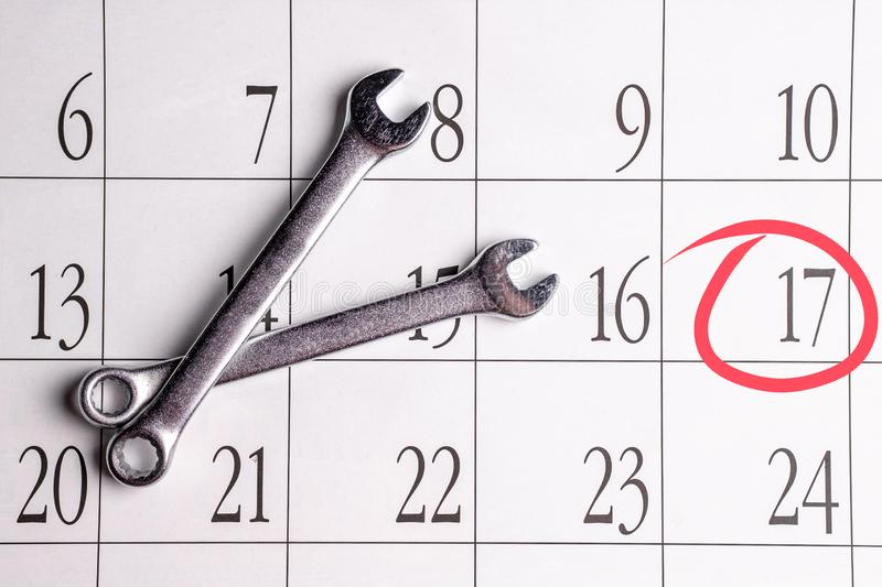 Two spanner tools for tightening the screws lie on each other on the background of the calendar with one date circled in red. The important date of repair royalty free stock image