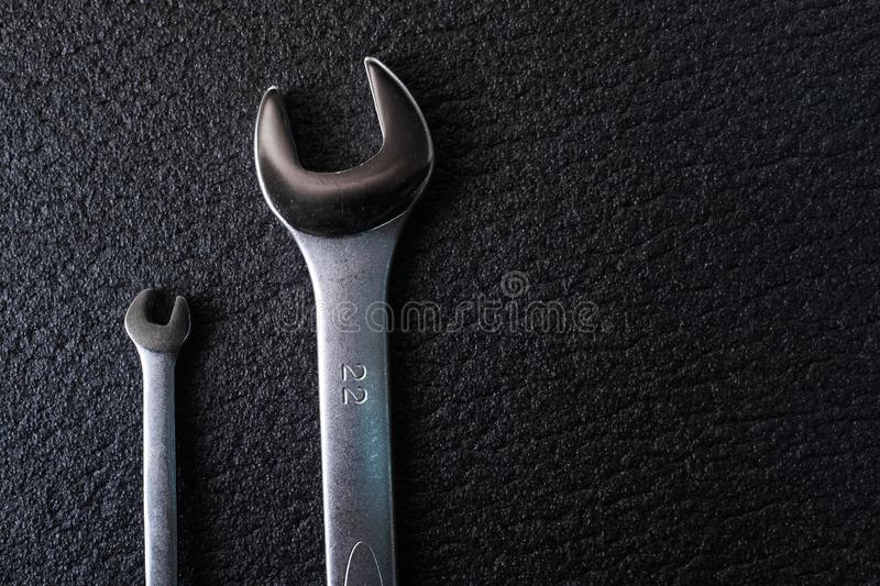 Two spanners wrench for professional car repair on a black wooden background royalty free stock photography