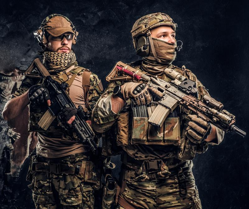 Two special forces soldiers in full protective equipment with assault rifles. Studio photo against a dark wall. Two special forces soldiers in full protective royalty free stock image