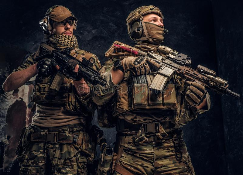 Two special forces soldiers in full protective equipment with assault rifles. Studio photo against a dark wall. Two special forces soldiers in full protective stock photo