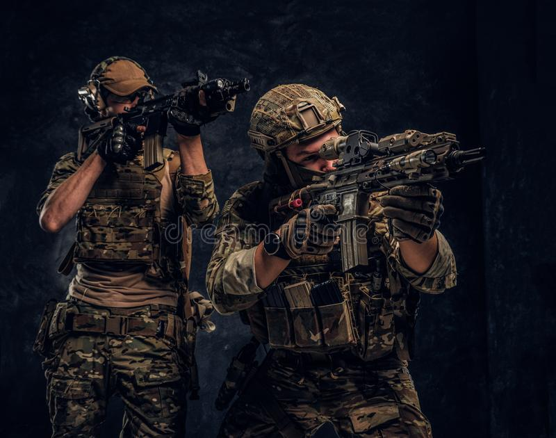 Two special forces soldiers in full protective equipment holding assault rifles and aiming at the targets. Studio photo royalty free stock photography