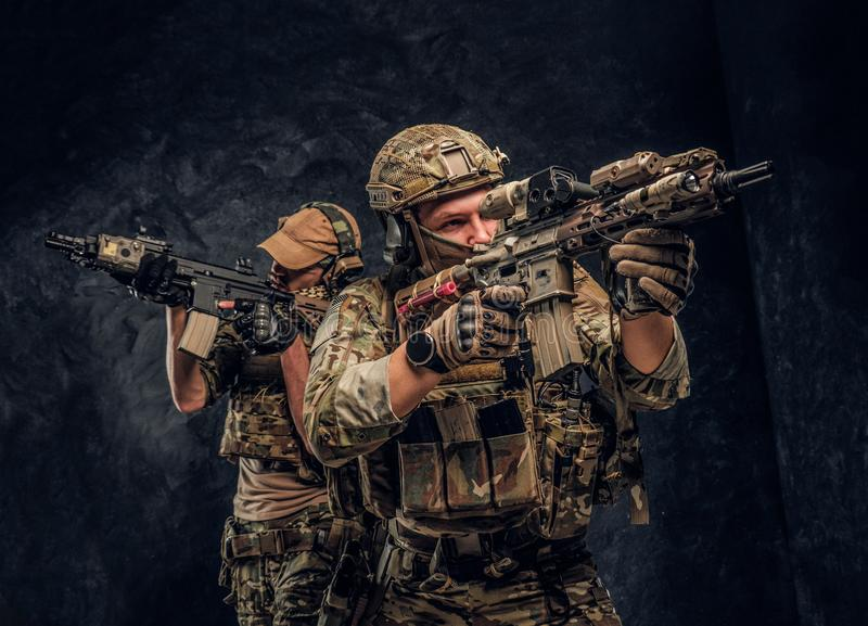 Two special forces soldiers in full protective equipment holding assault rifles and aiming at the targets. Studio photo stock photography