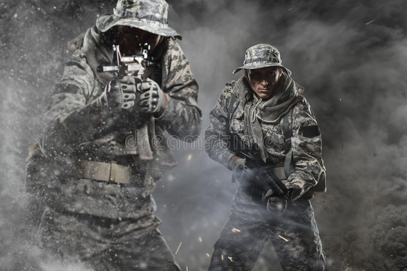 Two Special forces soldiers men holding a machine gun on dark background royalty free stock photos