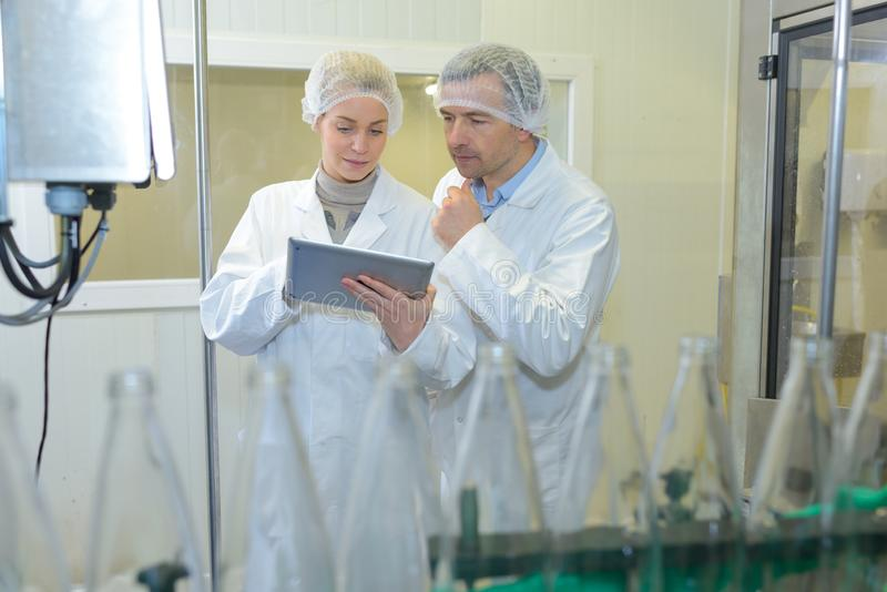 Two specialists in factory checking bottles royalty free stock photo