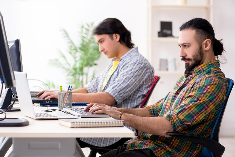 The two it specialists working in the office stock photo