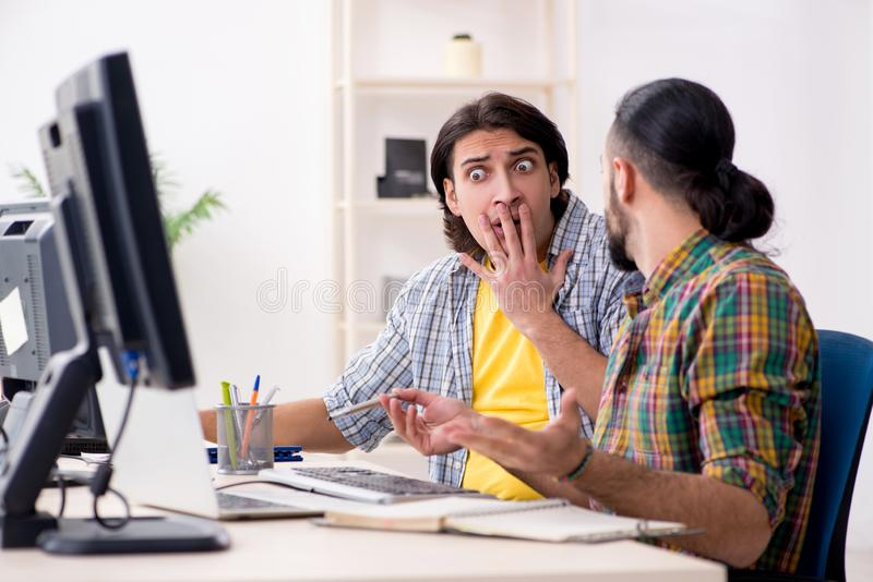 Two it specialists working in the office stock photo