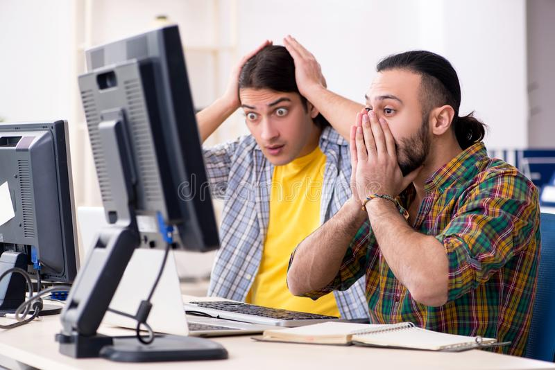 Two it specialists working in the office stock images