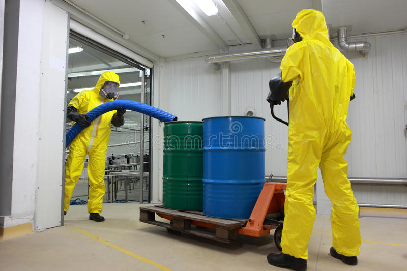 Two specialists working with toxic waste. Two specialists in protective uniforms,masks,gloves and boots working with barrels of toxic waste in factory royalty free stock photography