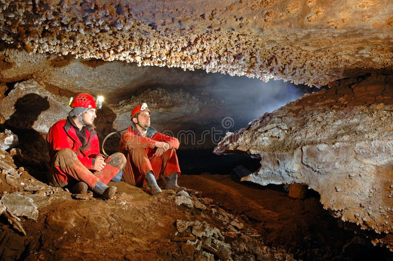Two spelunkers in a cave. Spelunkers in cave admiring the stalactites royalty free stock image