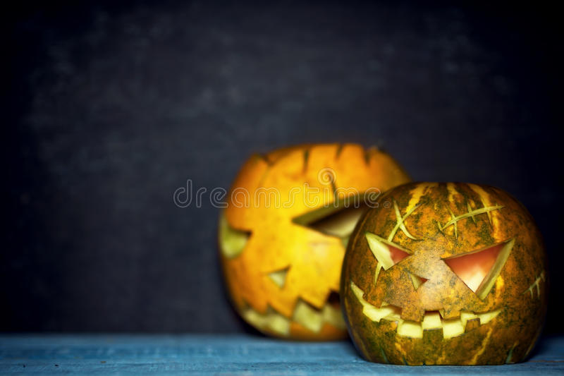 Two spooky pumpkin lanterns in darkness. Blue ang orange. Rustic halloween background. Text space royalty free stock images