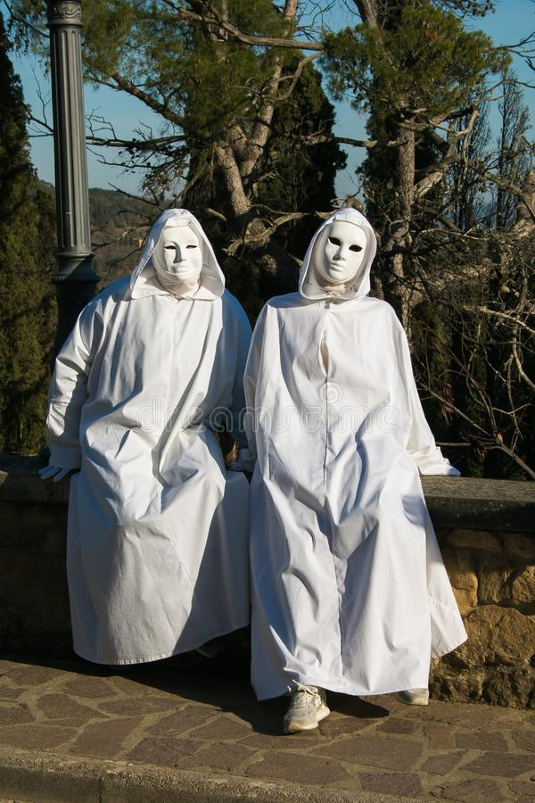 Two spooky white ghost with black eyes sitting in the wall of Castiglion Fibocchi stock photos