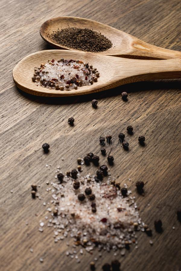 Two spoons with pepper and salt royalty free stock images