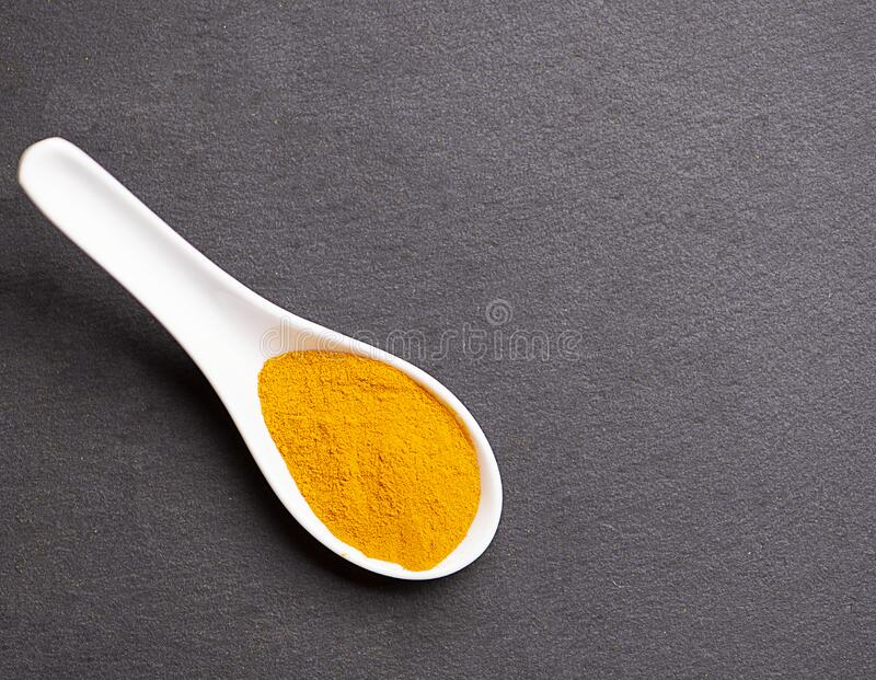 Two spoons with turmeric on black slate base. Healthy orange spice. royalty free stock photos