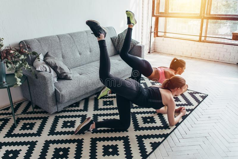 Two sportive female friends doing toning exercise performing donkey kicks at home royalty free stock photos