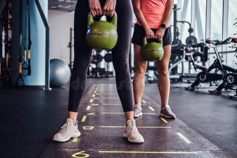 Two sportive girls trains with kettlebells in the modern gym. stock photography