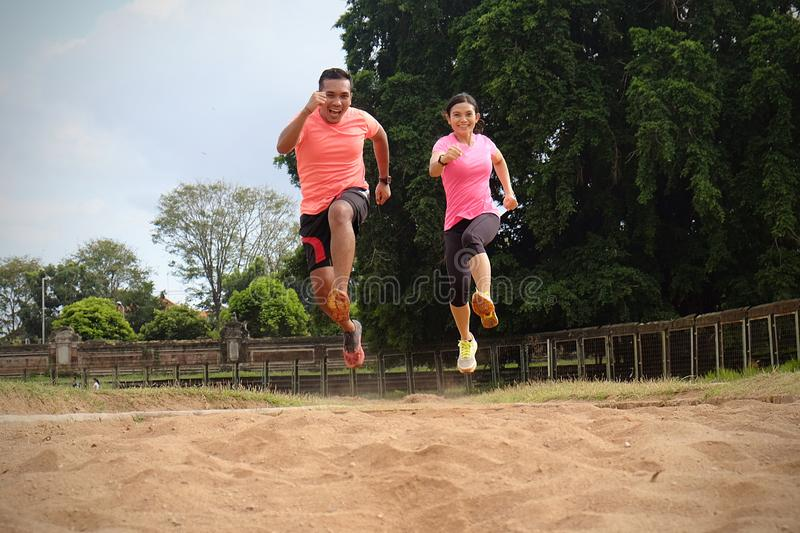 Two sports partners are jogging together on a sunny day wearing orange and pink shirts. They jumped and smiled at each other. They royalty free stock photography