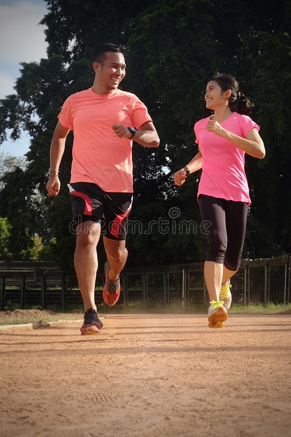 Two sports partners are jogging together on a sunny day wearing orange and pink shirts. They look at each other and smile, enjoy stock images