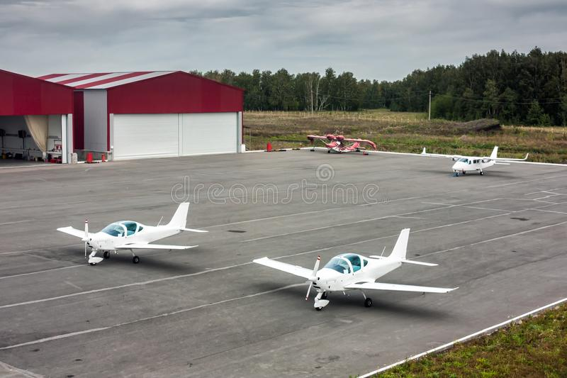 Two sports planes, one small passenger airplane and one amphibian aircraft. Parked near hangars royalty free stock image