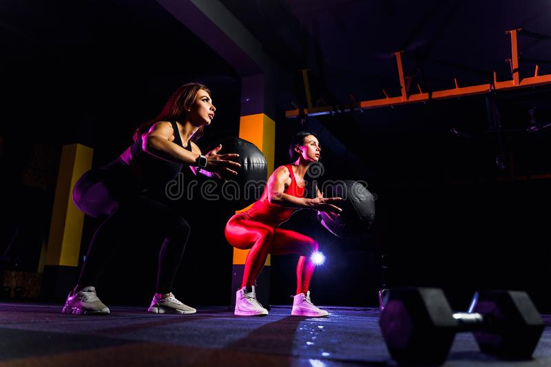 Two Sports women doing squat exercises with fitness ball. Female exercising and stretching with medicine ball at gym stock image