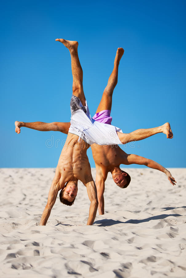 Two sportsmans on beach. On blue sky background stock photos