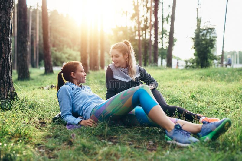 Two sporty girlfriends relaxing, lying on grass and chatting in the forest after jogging together stock photography