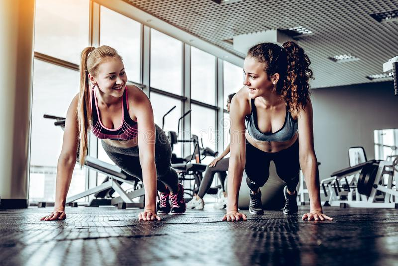 Two sporty girls doing push ups. Two sporty girls doing push ups at gym. Fitness, sport, exercising and people concept stock images