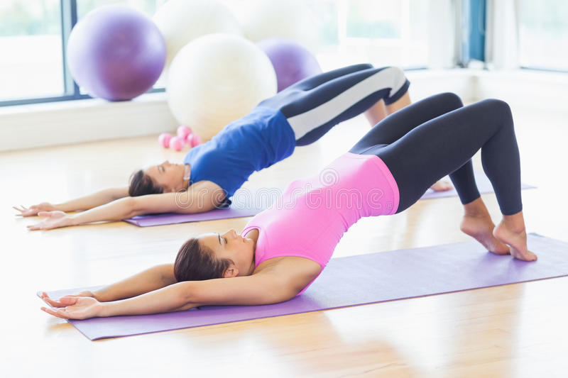 Two sporty women stretching body at yoga class. Two sporty young women stretching body at yoga class in fitness studio royalty free stock photo