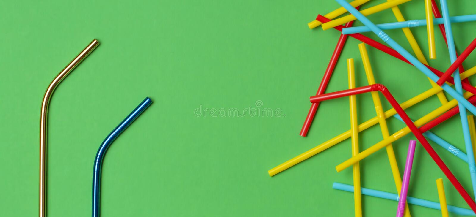 Two stainless steel reusable drinking straws with many multicolored plastic straws on green background. No plastic, zero. Two stainless steel reusable drinking stock image